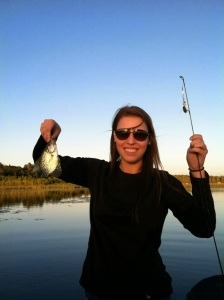 woman in sunglasses holding up small fish and pole