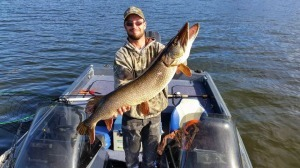 man in camo holding up very big musky