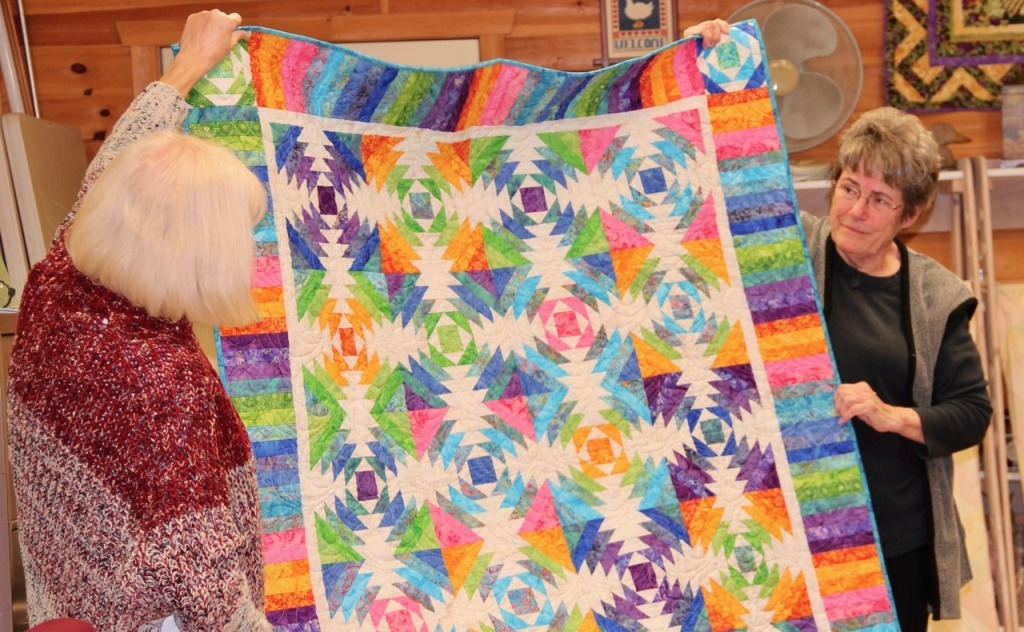 Quilters sharing their work at Monika's Quilt & Yarn Shop
